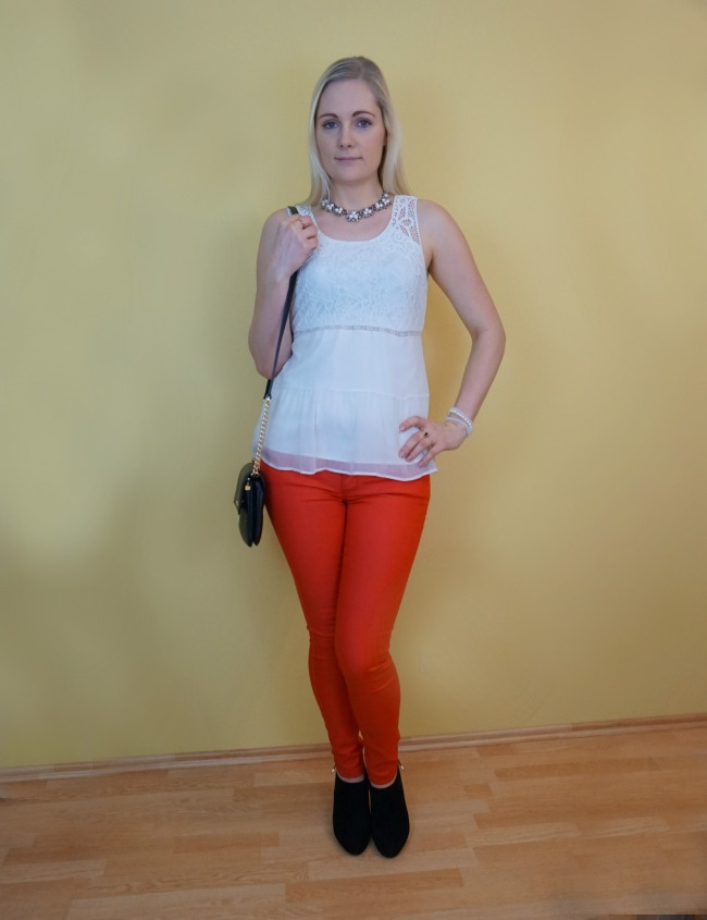 red pants, white top, black heels, black crossbody bag