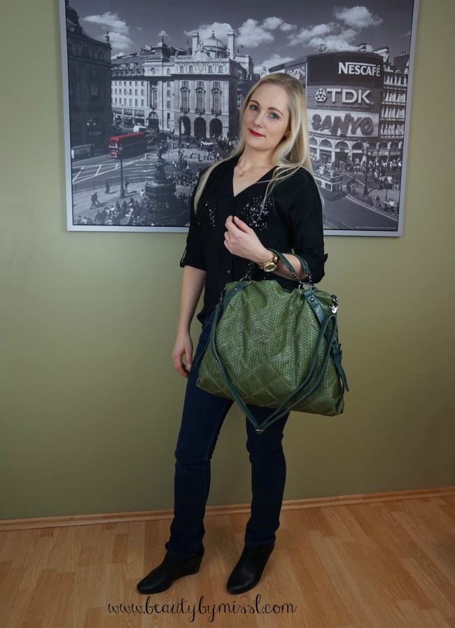 green bag, black blouse and dark blue jeans