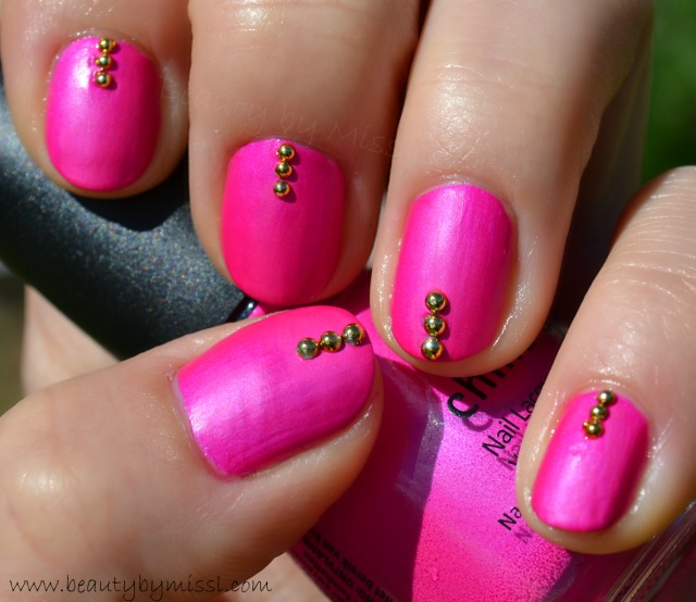 fuchsia pink manicure with golden decorations