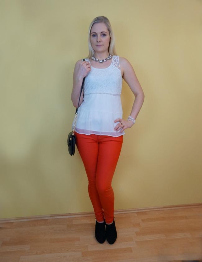 red pants, white top, black heels, black crossbody bag