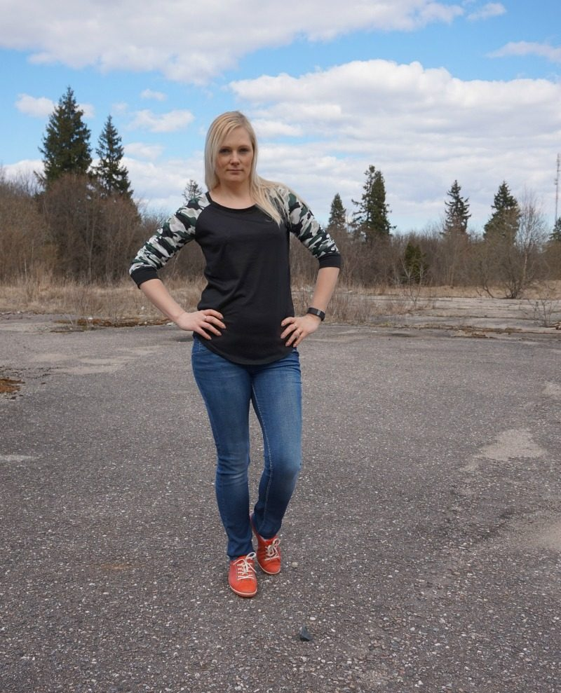 black and camouflage detail top, blue jeans, red shoes