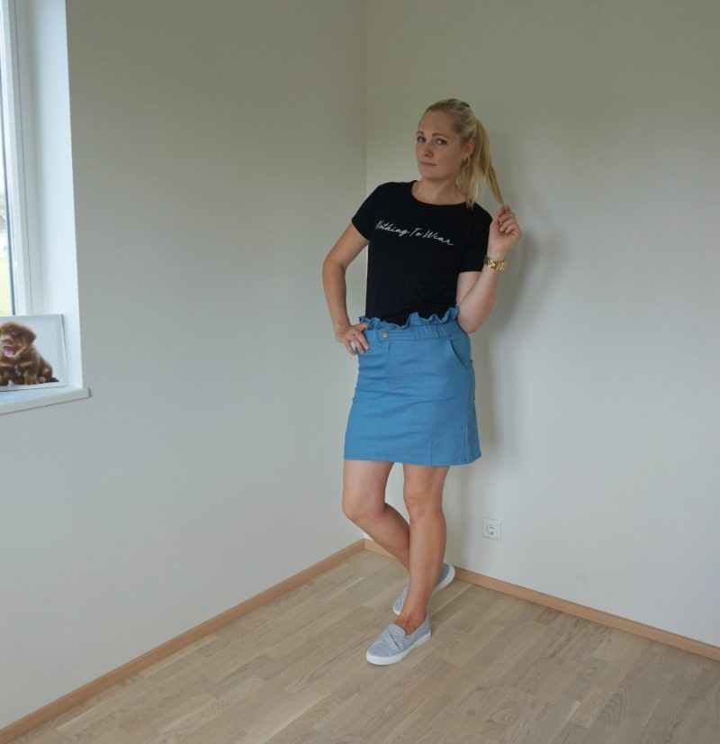 black tee and blue paperbag skirt and slip on trainers