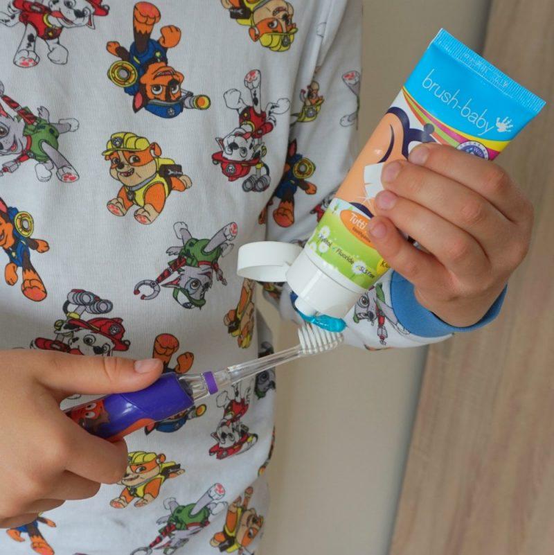 putting Baby Brush Tutti-Frutti toohpaste on a KidzSonic electric toothbrush