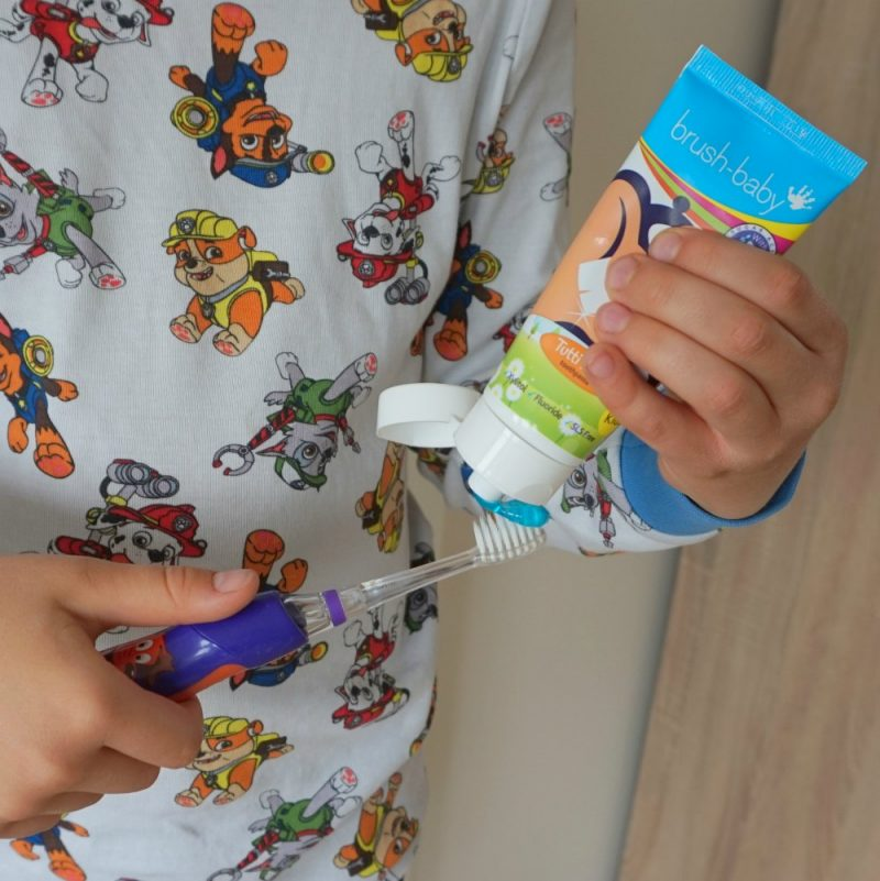 putting Baby Brush Tutti-Frutti toohpaste on a KidzSonic electric toothbrush