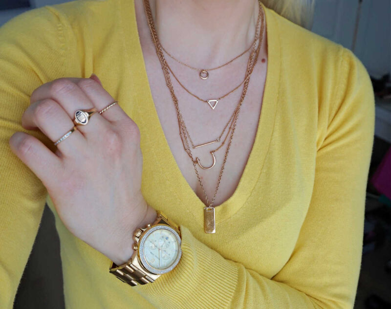 golden layered necklace and gold watch