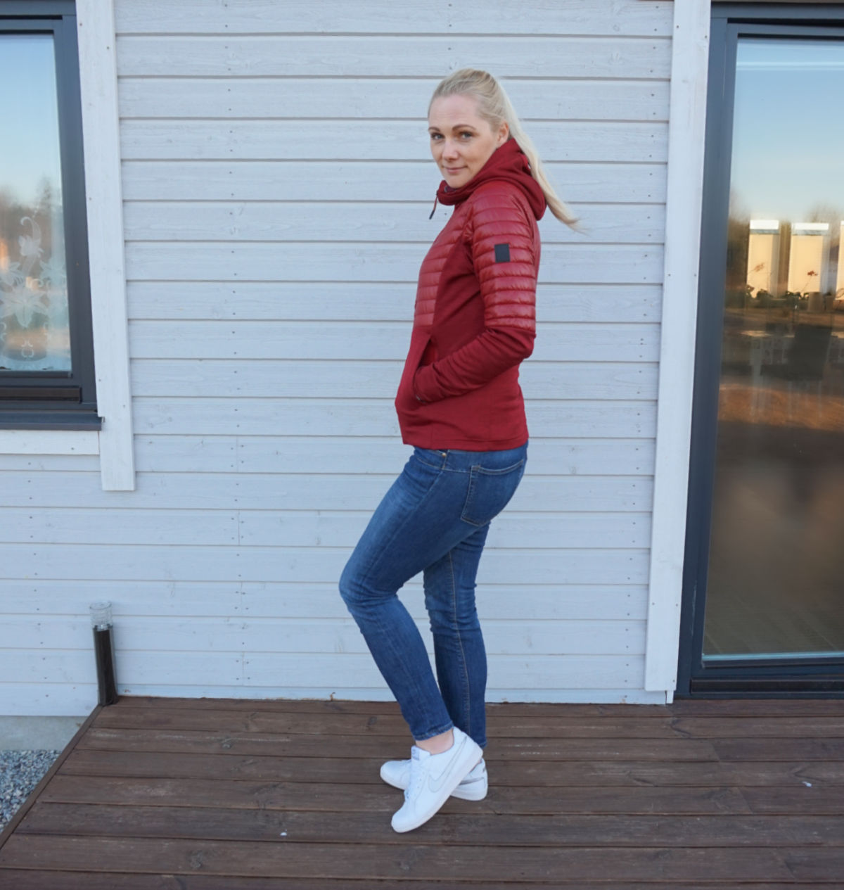 Didriksons Annema jacket paired with blue skinny jeans and white trainers.