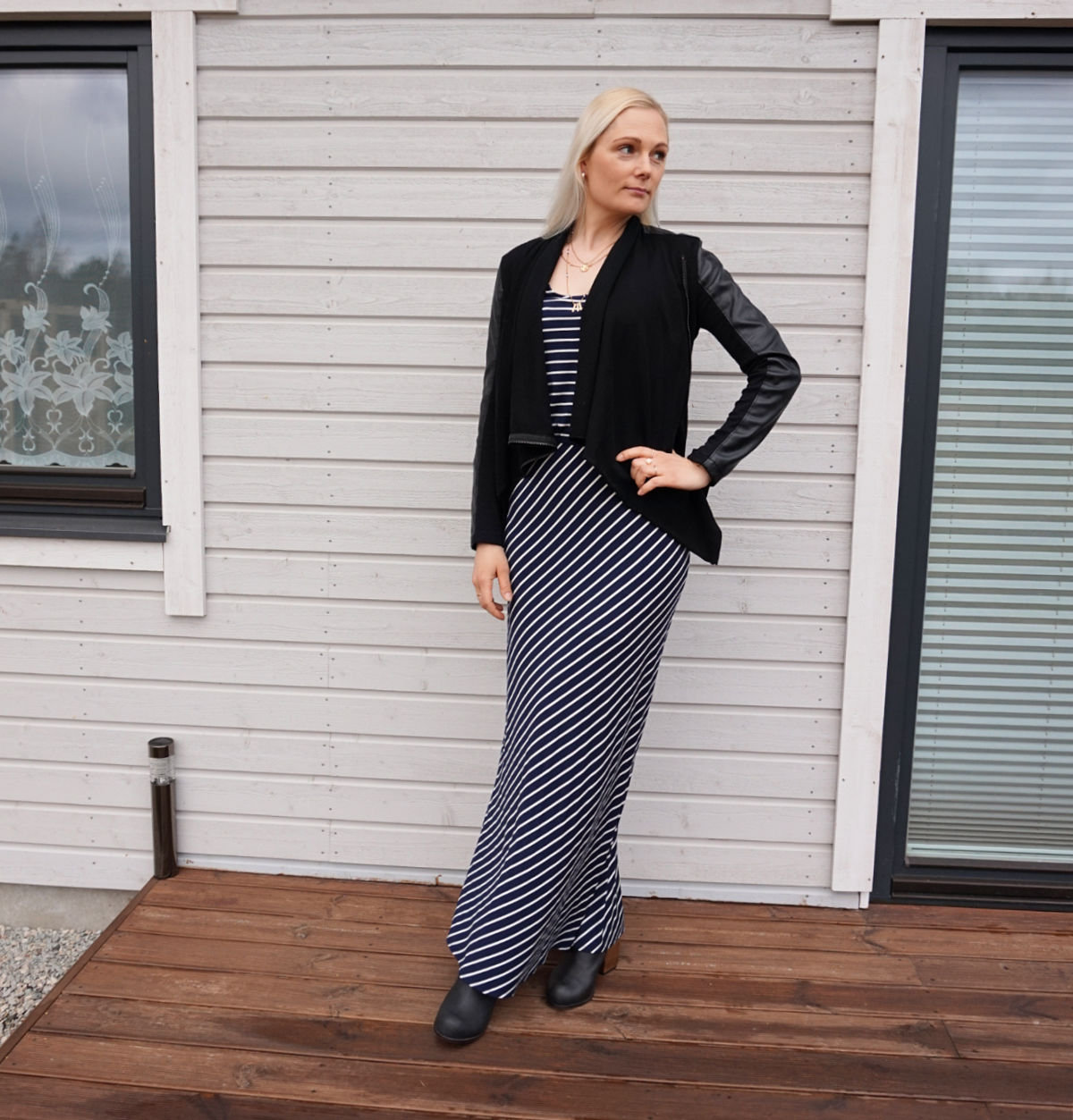 Navy and white striped maxi dress paired with a black vegan leather jacket and ankle booties.