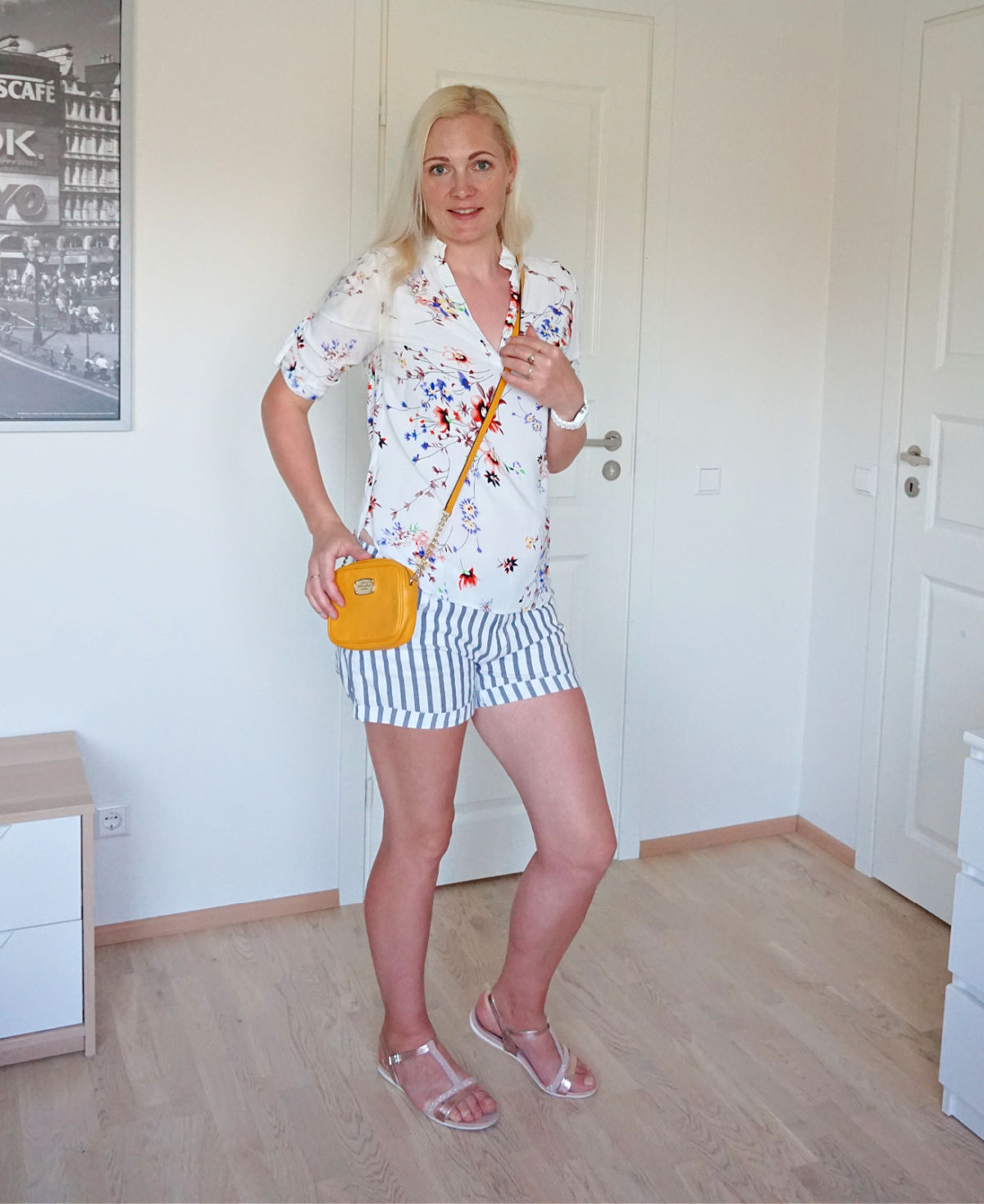 Striped shorts ad floral blouse accessorized with a pair of rose gold sandals and yellow crossbody bag.